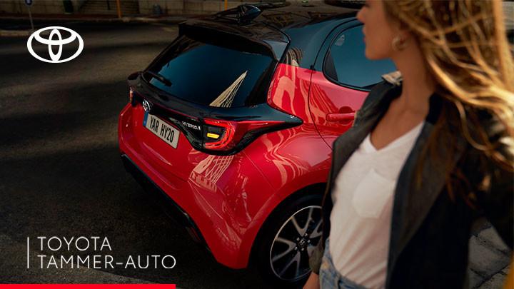 Punainen auto takana ja ihminen sen edessä.