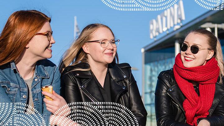 Hymyilevät ihmiset istuvat Ratinan kauppakeskuksen edessä.